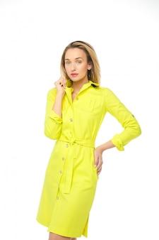 Jeune mannequin en robe jaune posant à la caméra.