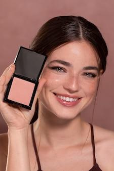 Jeune mannequin tenant une boîte à blush