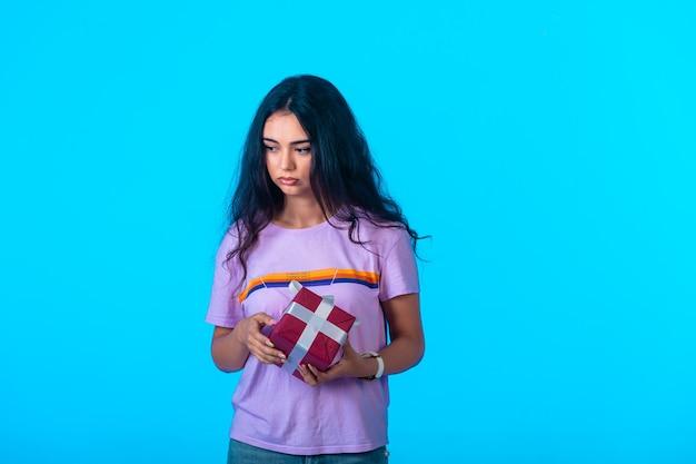 Jeune mannequin tenant une boîte cadeau rouge mais a l'air déprimé