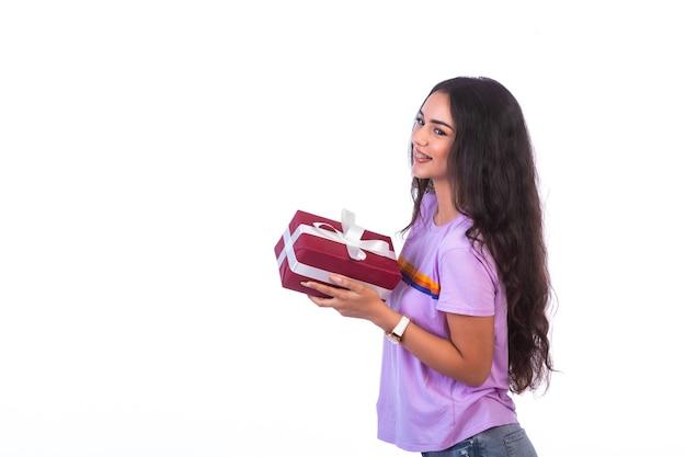 Jeune mannequin tenant une boîte cadeau rouge, vue de profil.