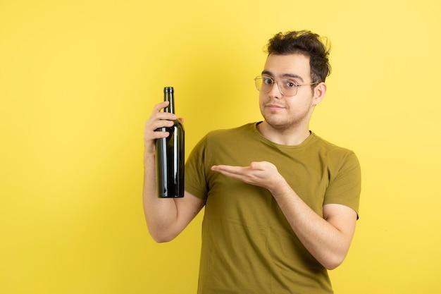Jeune mannequin tenant une bouteille de vin blanc.