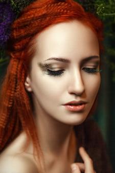 Jeune mannequin tête rouge pose avec un maquillage créatif