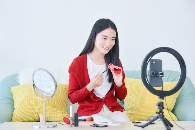 Jeune maquilleuse asiatique, vlogueuse beauté ou blogueuse enregistrant un tutoriel de maquillage cosmétique vlog
