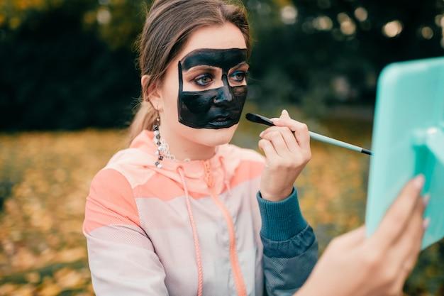 Jeune maquilleuse dessinant sur son visage avec aquarelle