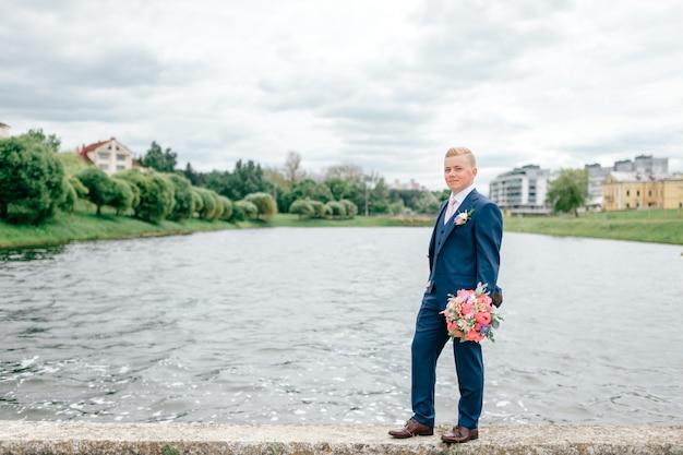Jeune marié avec bouquet de fleurs dans sa main posant en plein air avec lac sur fond