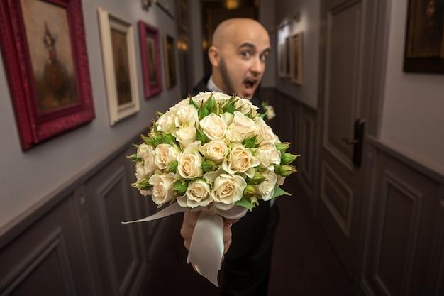 Jeune marié drôle avec le beau bouquet de mariage des roses