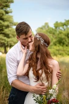 Le jeune marié se tient derrière la mariée, la serre dans ses bras et lui embrasse le nez