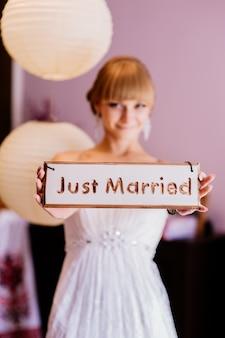 Jeune mariée blonde le jour de son mariage tient une planche de bois avec l'inscription vient de se marier. concept d'amour. mariage en enseigne.