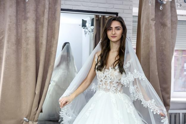Jeune mariée en charmante robe de mariée en boutique