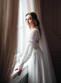 Une jeune mariée dans une belle robe en dentelle boho se tient à la fenêtre.