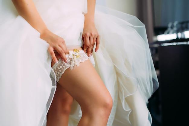 Jeune mariée dans une robe blanche avec une jarretière de mariage sur sa jambe, gros plan. préparation pour la célébration du mariage. accessoires pour les jeunes mariés, jarretière en dentelle.