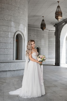 Jeune mariée élégante en robe de mariée classique posant avec un bouquet de mariée à l'extérieur modèle féminin en...