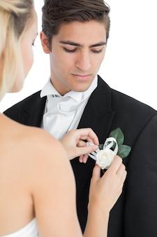 Jeune mariée épingler une fleur sur son costume de maris