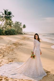 Jeune mariée est debout sur une plage tropicale