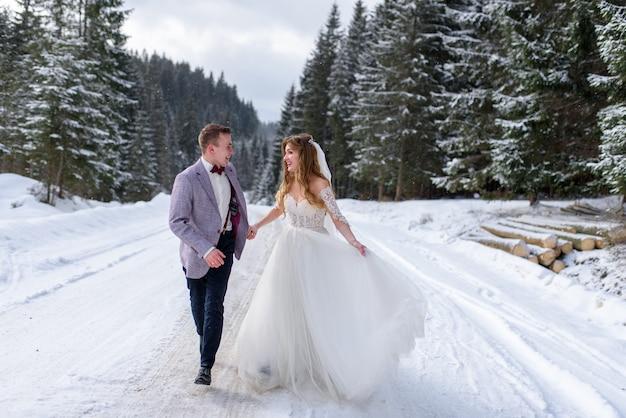 Jeune mariée et le marié sur la forêt enneigée