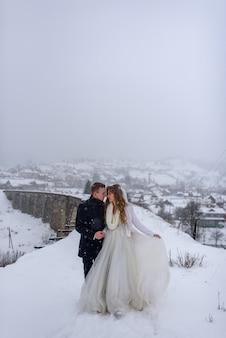 Jeune mariée et le marié sur la montagne enneigée