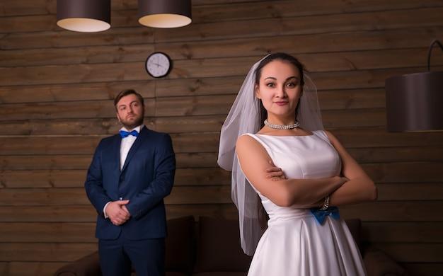 Jeune mariée et marié sérieux sur chambre en bois