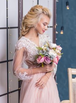 Jeune mariée mode beauté dans un décor d'hiver avec bouquet de fleurs dans ses mains. maquillage et coiffure de mariage belle mariée portrait.
