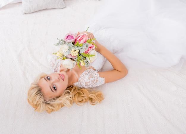 Jeune mariée de mode beauté sur le décor de lit avec bouquet de fleurs dans ses mains. maquillage et coiffure de mariage belle mariée portrait. magnifique mariée de beauté.