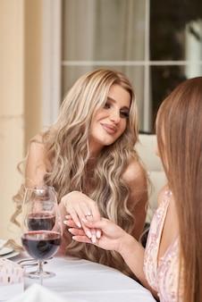 Jeune mariée montre une alliance à ses amis