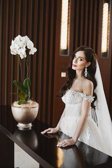 Jeune mariée sexy avec un corps parfait et de gros seins dans la robe de mariée à la mode et dans de grandes boucles d'oreilles de luxe posant à l'intérieur de luxe