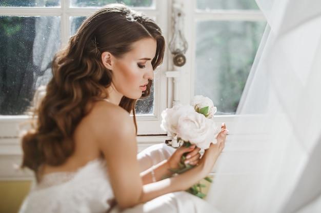Jeune mariée tient un bouuqet de pivoines sur le rebord de la fenêtre dans la matinée lumineuse