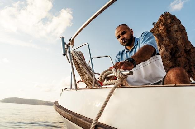 Jeune marin afro-américain attachant des cordes sur un voilier en mer au coucher du soleil