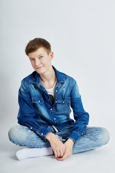 Jeune mec adolescent assis dans un jean bleu sur le sol