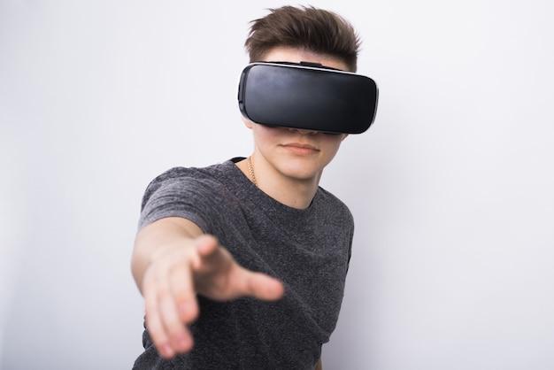 Un jeune mec, un adolescent se tient dans une villard vr lunettes sur un fond blanc
