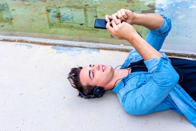 Jeune mec au casque noir allongé sur le sol faisant un selfie