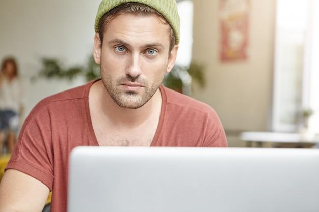 Jeune mec aux yeux bleus et à la barbe regarde en toute confiance assis devant un ordinateur portable ouvert, vérifie ses e-mails ou surfe sur les réseaux sociaux en ligne