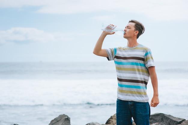 Jeune mec boire de l'eau sur la plage