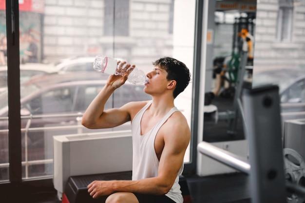 Jeune mec buvant dans la salle de sport