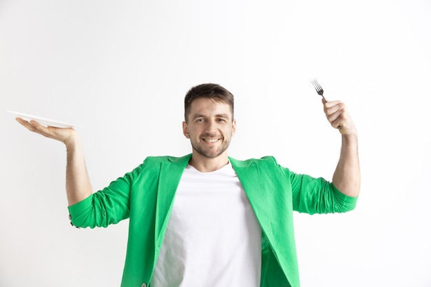 Jeune mec caucasien attrayant souriant tenant un plat vide et une fourchette isolé sur fond gris. copiez l'espace et simulez. arrière-plan du modèle vierge.