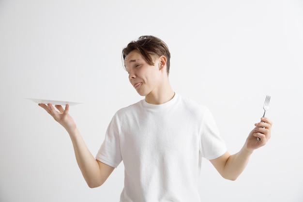 Jeune mec caucasien attrayant triste tenant un plat vide et une fourchette isolé sur fond gris. copiez l'espace et simulez. arrière-plan du modèle vierge. rejeter