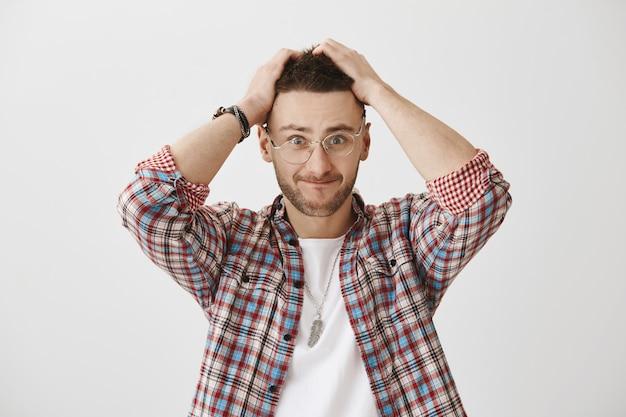 Jeune mec confus et tendu avec des lunettes posant