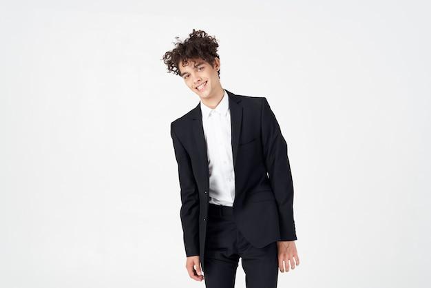 Jeune mec dans un costume classique sur un fond clair portrait de cheveux bouclés vue recadrée