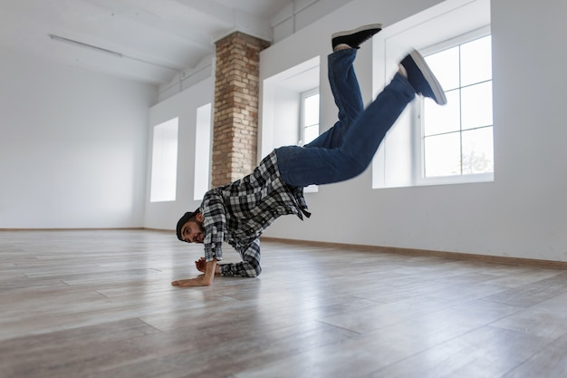 Jeune mec élégant danseur avec un jean et une chemise dansant dans un studio de danse lumineux