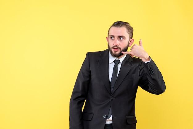 Jeune mec avec une expression faciale sérieuse montrant le geste de me contacter