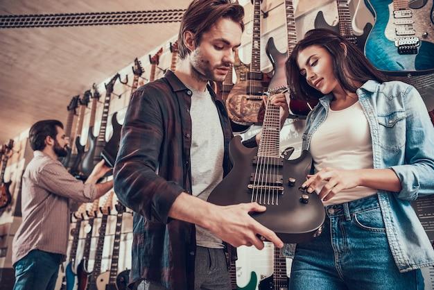 Jeune mec fait la démonstration de guitare électrique à une jeune fille