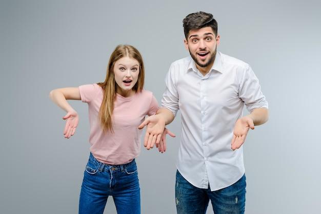 Jeune mec et fille pointant vers le bas isolé