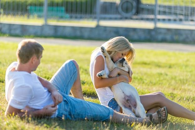 Jeune mec avec une fille promenant son chiot retriever dans le parc en été.