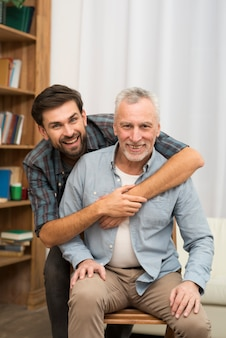 Jeune mec heureux embrassant un homme âgé sur une chaise