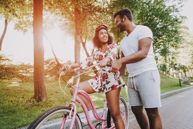 Jeune mec latin enseigne à sa copine à faire du vélo