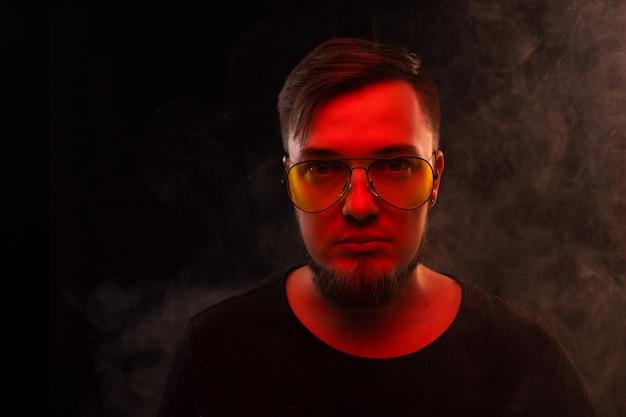 Jeune mec à lunettes dans un nuage de fumée avec lumière rouge.