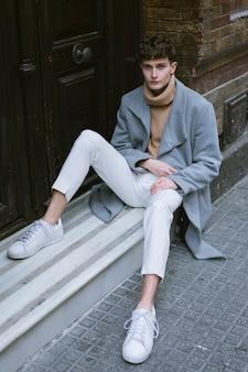 Jeune mec avec manteau assis devant la porte