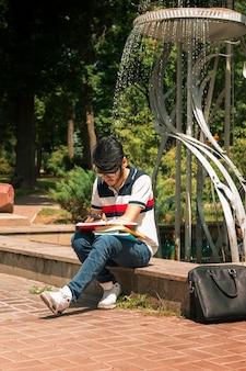 Jeune mec de la mode assis près de la fontaine et lit des livres