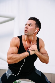 Jeune mec musclé se prépare à faire de l'exercice, faire des exercices physiques, écouter de la musique