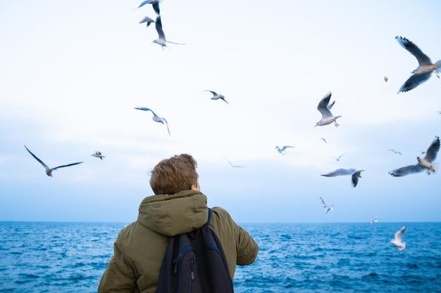 Jeune mec nourrir les mouettes au bord de la mer