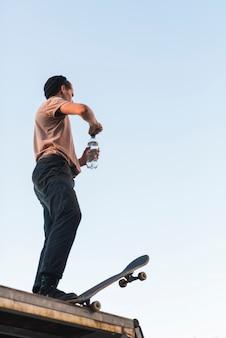 Jeune mec posant avec une planche à roulettes et une bouteille d'eau
